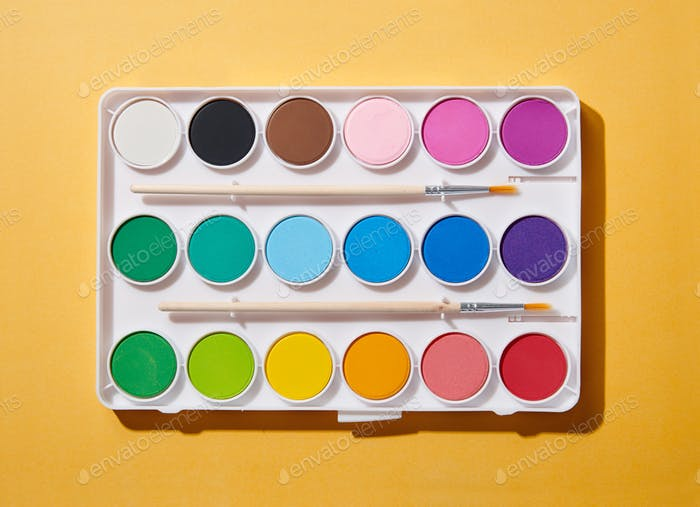 Open new watercolor paint box with brushes