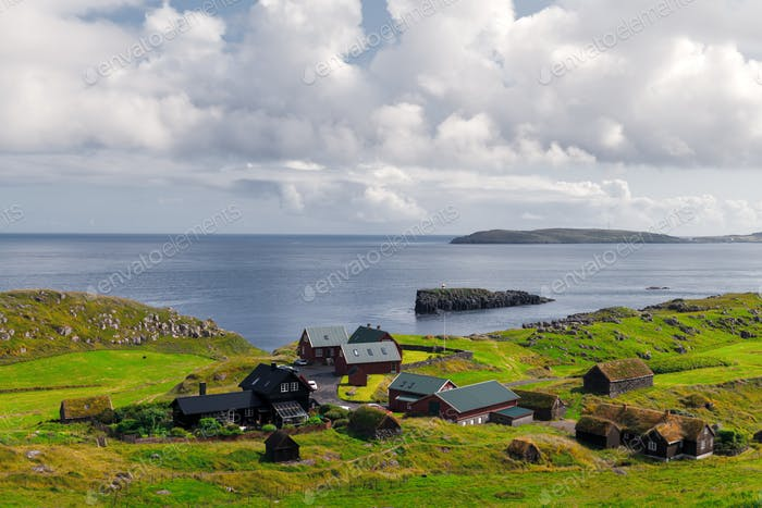 Summer view of small village with typical faroese turf-top houses
