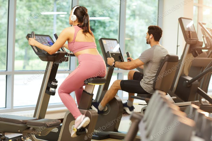 People using Exercise Machines in Gym