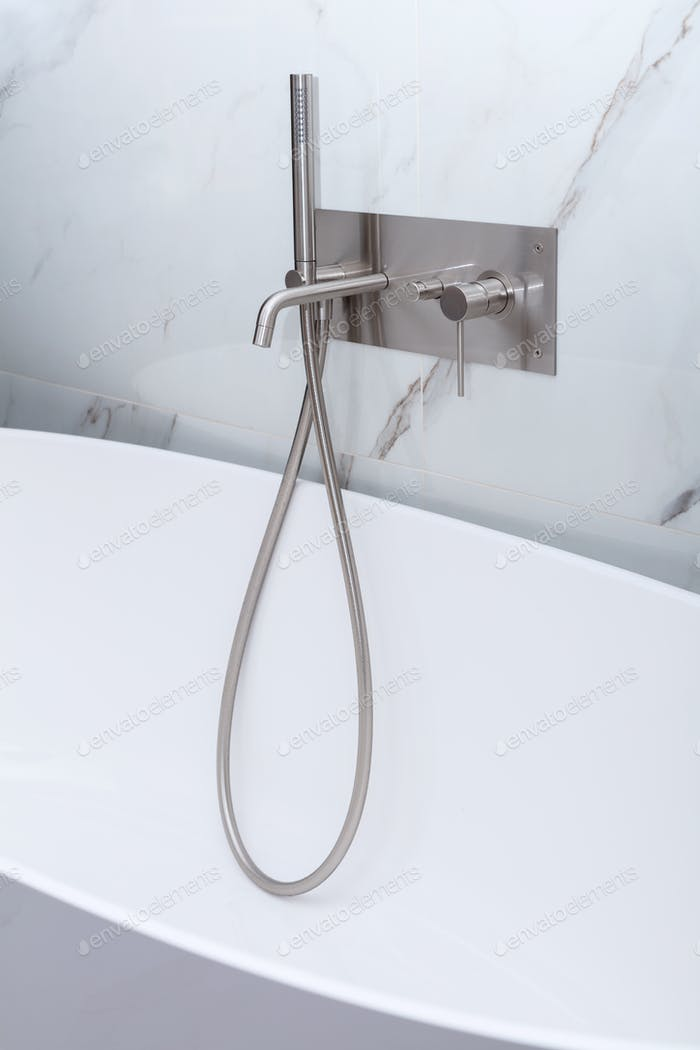 Modern new luxury bath tub with stainless steel shower and faucet.