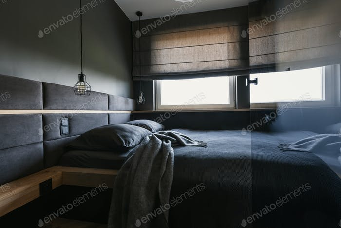 Cozy, dark bedroom interior with gray sheets and blanket and a f