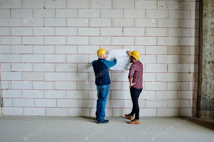 Two professional engineers in hardhats standing by wall and discussing sketch