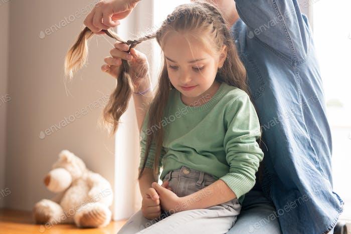 Braiding hair of daughter