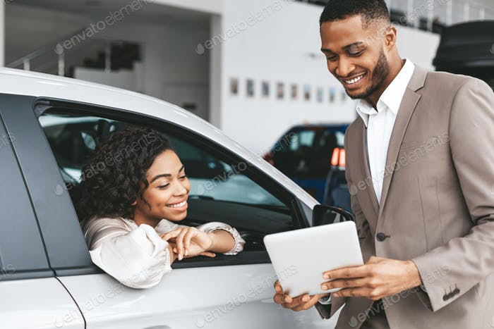 African American Woman Buying Car In Auto Dealership Center