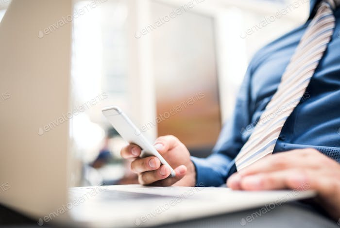 A young businessman with laptop and smartphone, working.