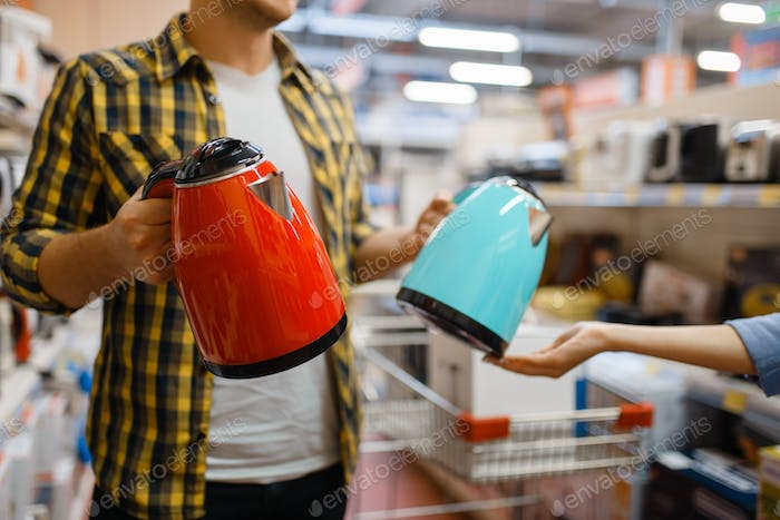 Couple choosing electric kettle, electronics store