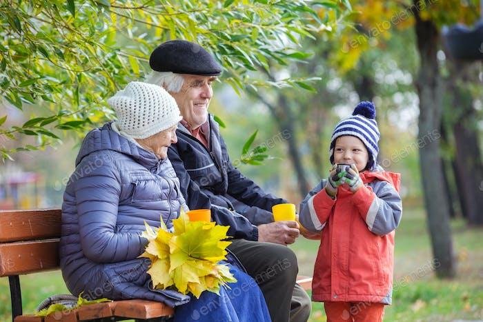 Großeltern und Enkel trinken heißen Tee im Herbstpark