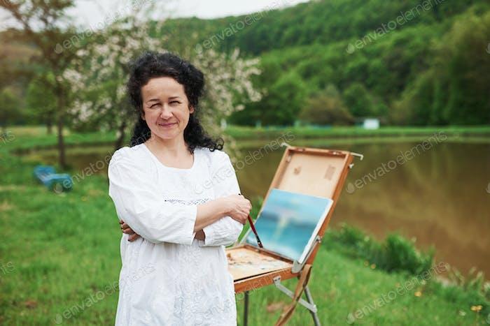 Портрет зрелого художника с черными вьющимися волосами в парке на открытом воздухе