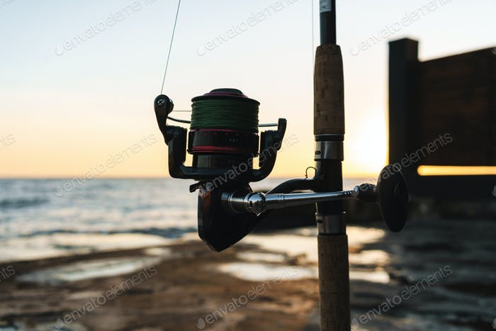 Close up of a fishing rod silhouette at the seashore