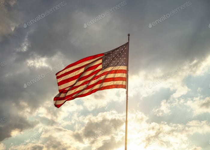 Back lit American flag waving under clouds with sun rays at sunset