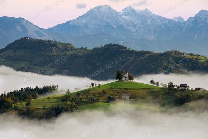 St. Thomas church at sunrise in the fog in Slovenia