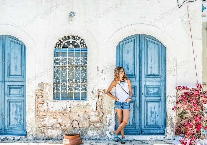Young blond woman at typical greek traditional town