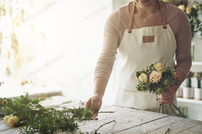 Florist arranging a bouquet of roses in her flower shop