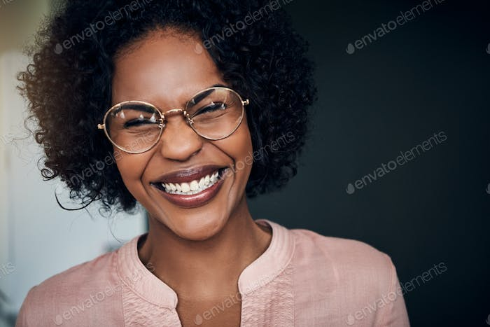 Laughing young African businesswoman standing alone in a modern office