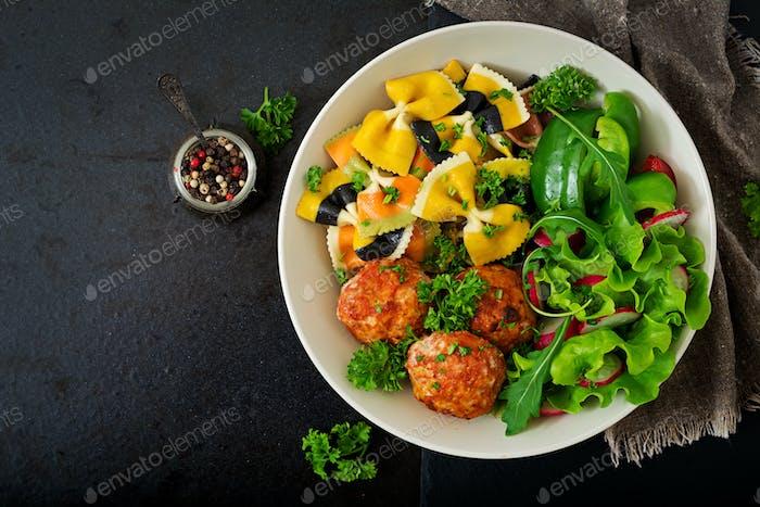 Farfalle pasta durum wheat with baked meatballs of chicken fillet  in tomato sauce