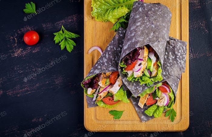 Tortilla mit Tinte Tintenfisch Wraps mit Huhn und Gemüse auf weißem Hintergrund.