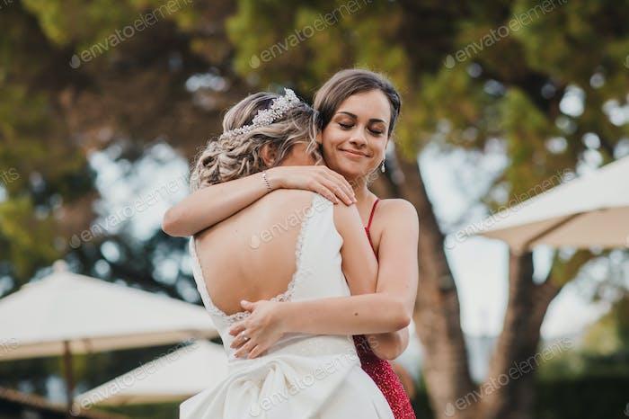 Brautjungfer umarmt die Braut bei der Hochzeit