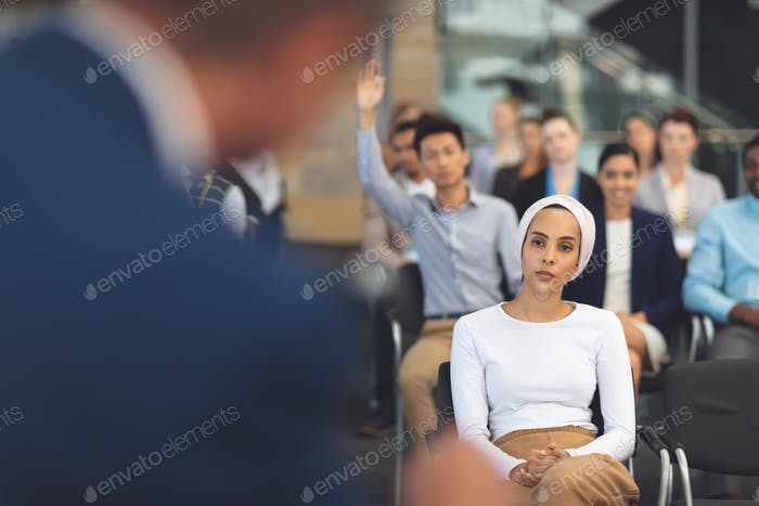 Business people listening to businessman speak at business seminar