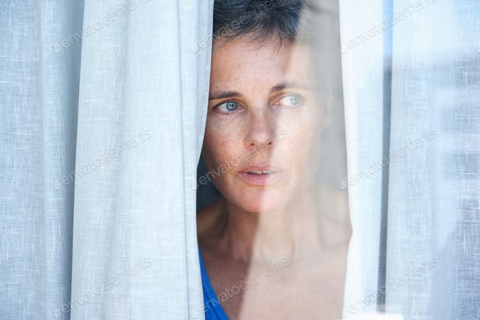 Close up older woman looking opening curtains and looking through window