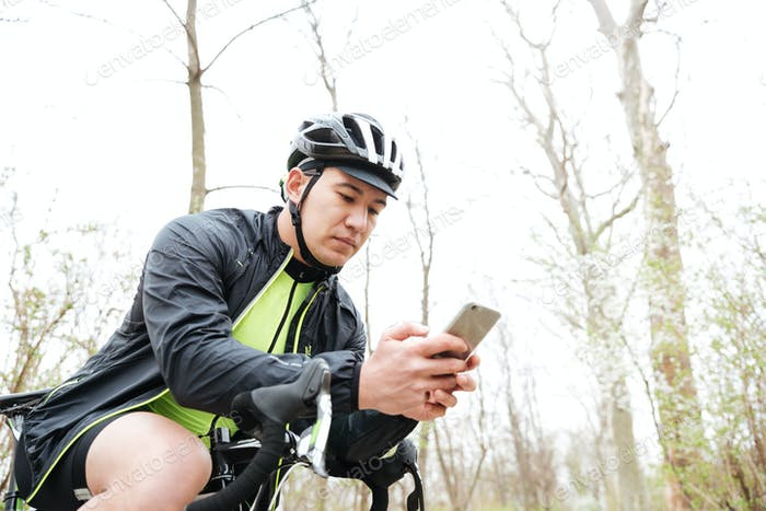 Man in cycling helmet with bicycle using smartphone in park