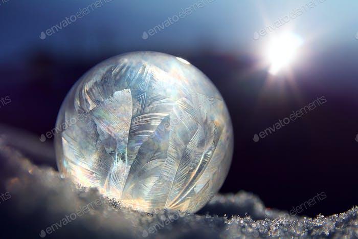 Frozen soap bubble ball on winter snow