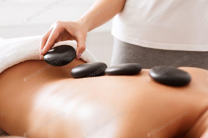 Masseuse doing hot stones massage to female client