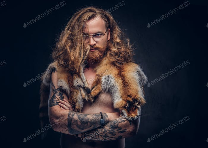 Tattooed redhead hipster male with the fox skin on a shoulder in a studio