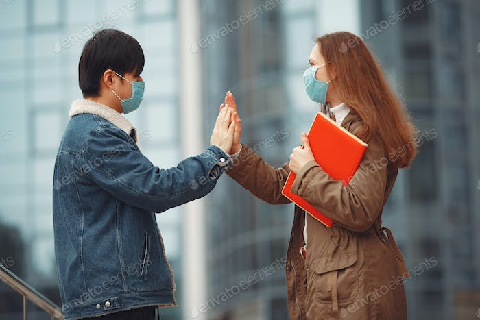 Chinese man and a woman in disposable masks are giving five each other