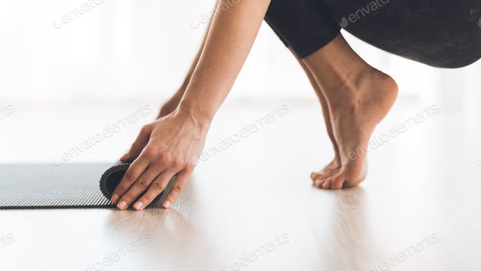 Yoga concept. Woman rolling up yoga mat after training