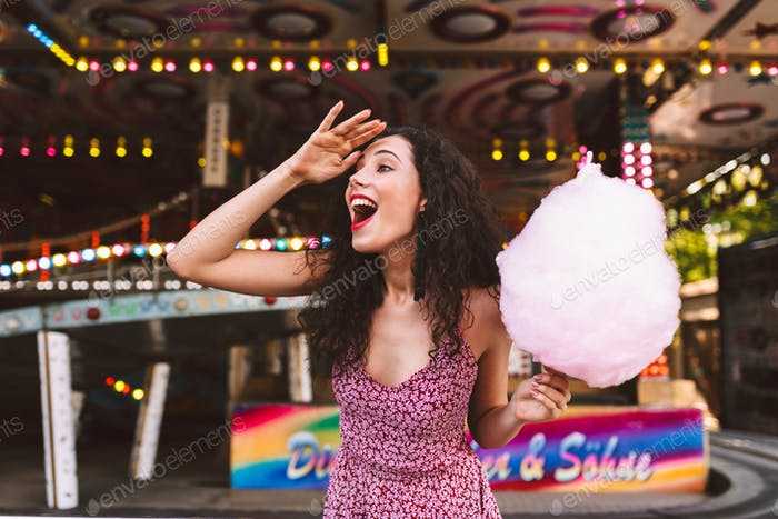 Joyful girl holding pink cotton candy happily looking aside in amusement park