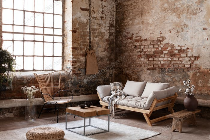 Armchair and beige sofa in industrial living room interior with