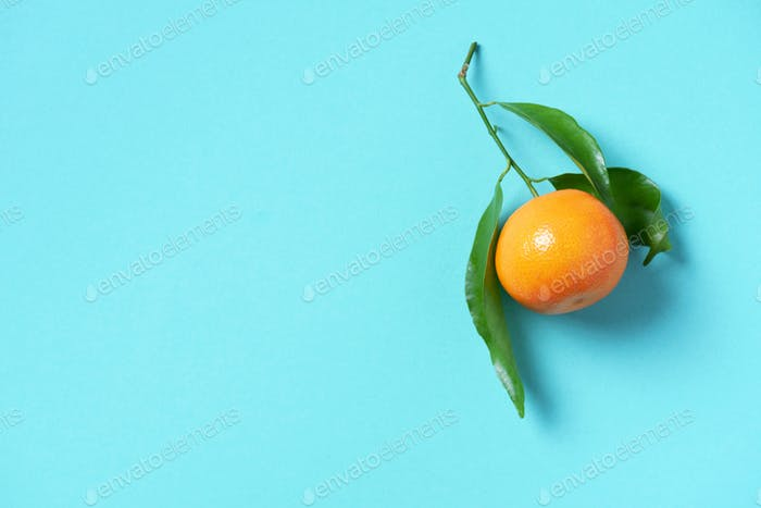 Tangerine or clementine with green leaf on blue background. Top view. Copy space. Christmas or New