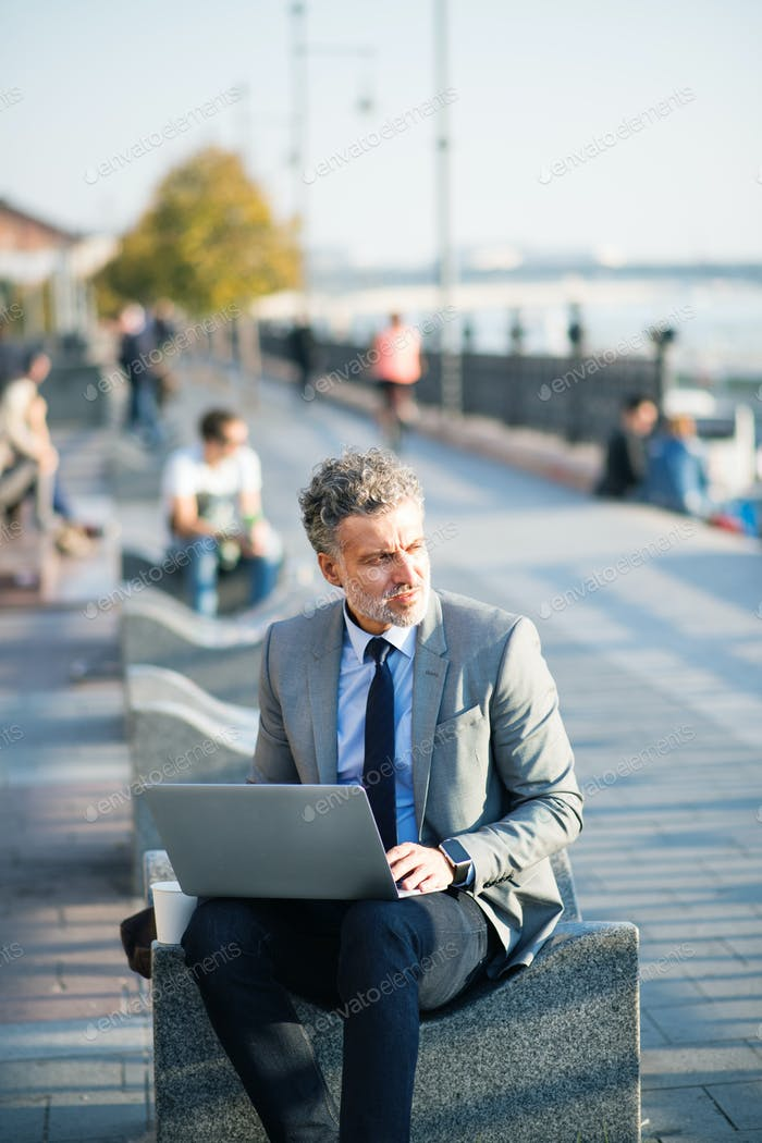 Mature businessman with laptop in a city.