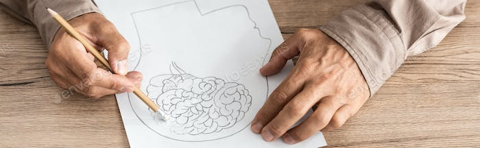 panoramic shot of retired man with alzheimer disease drawing human head and brain