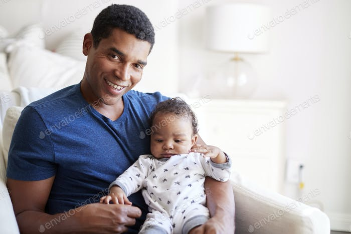 Close up of young adult black father sitting in an armchair holding his three month old baby son