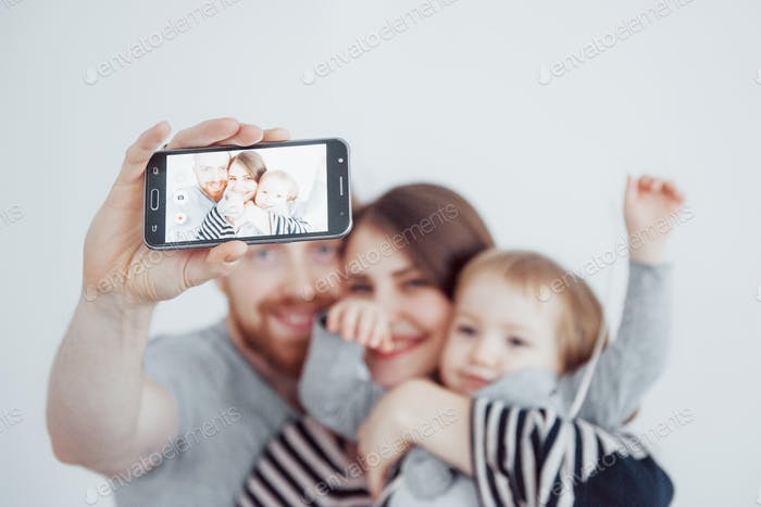 smiling mother, father and little girl making selfie with camera over white background