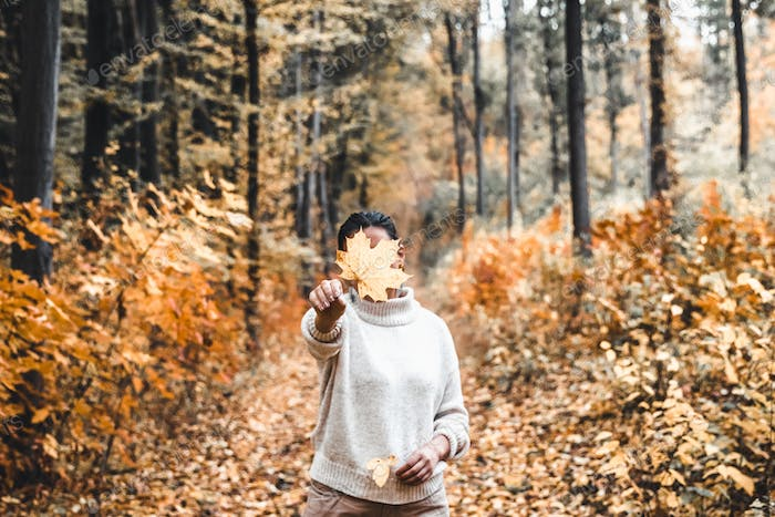 Woman covers her face with dry yellow leaf in autumn forest