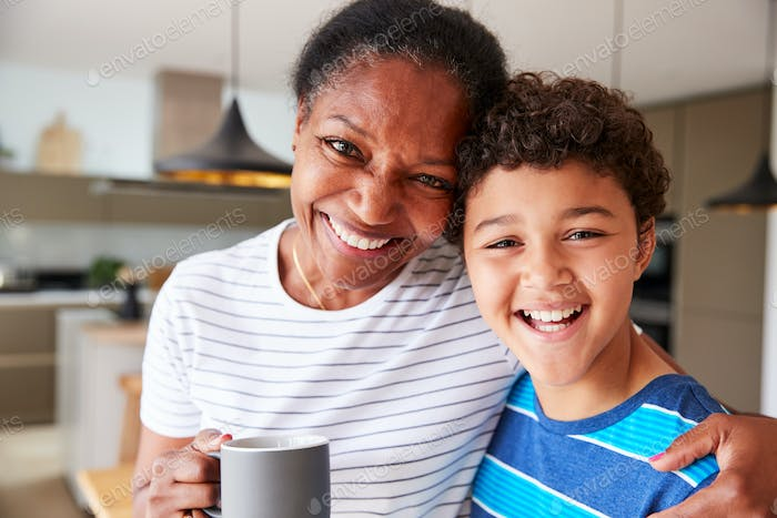Portrait Of Grandmother Drinking Coffee With Grandson In Kitchen At Home