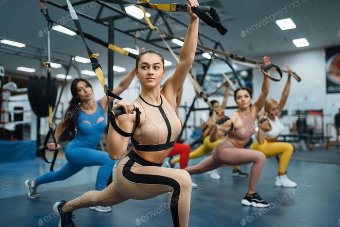 Group of muscular women doing exercise in gym