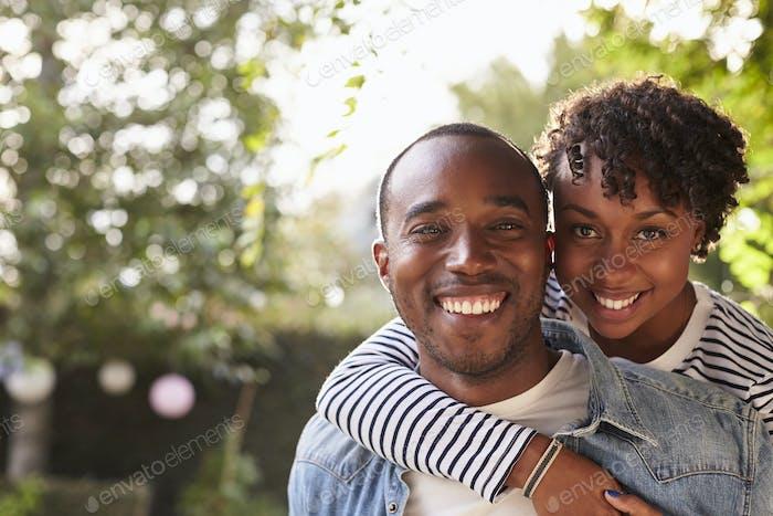 Happy young black couple piggyback in garden, look to camera