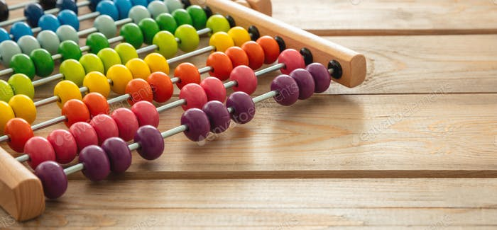 School abacus with colorful beads on wooden desk, close up view