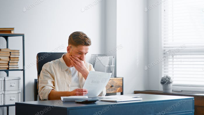 Skilled bearded accountant in yellow shirt looks through reports on sheets of papers