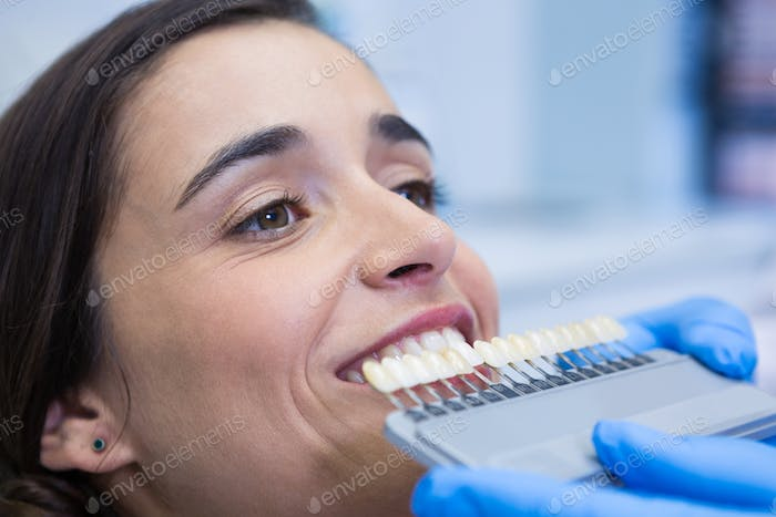 Close up of dentist holding equipment while examining woman at clinic