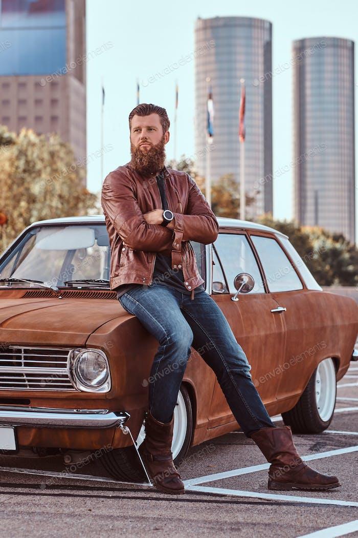 Бородатый мужчина, одетый в коричневую кожаную куртку и сапоги с настроенным ретро автомобиль