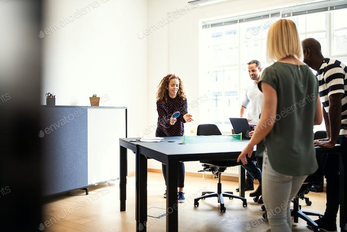 Young designers playing table tennis during an office meeting