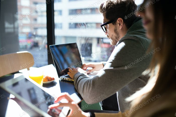 Beautiful young couple working with laptop in the coffee.