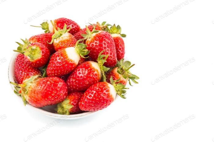 Plateful of freshly harvested organic strawberries with white ba