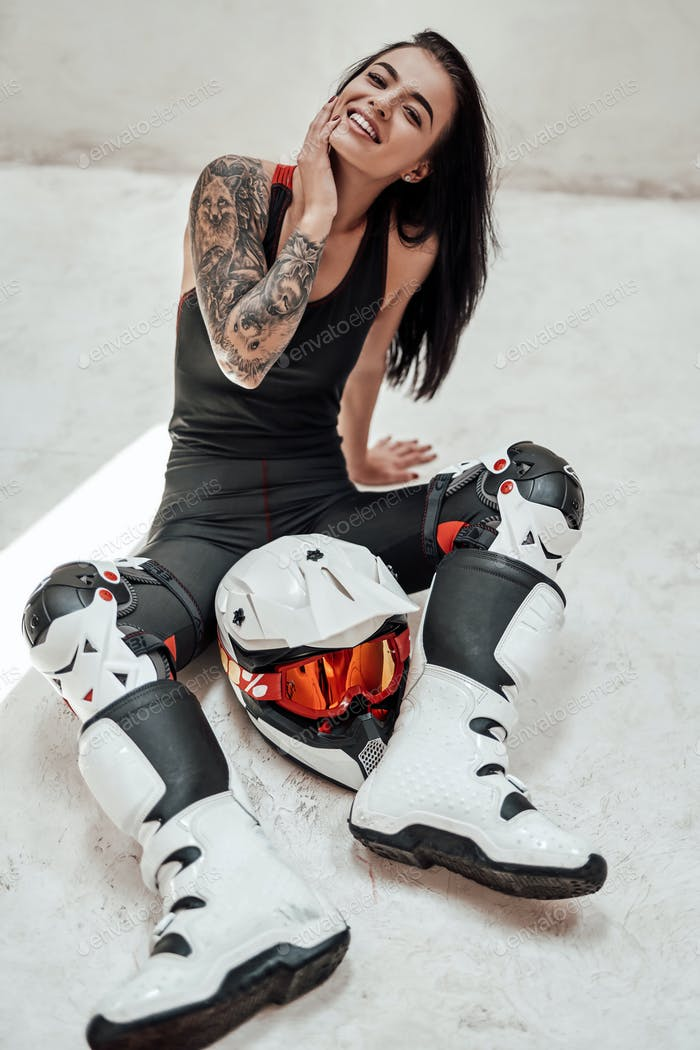 Glücklich lächelnde Brünette in einem Trainingsanzug posiert in einem weißen Fotostudio