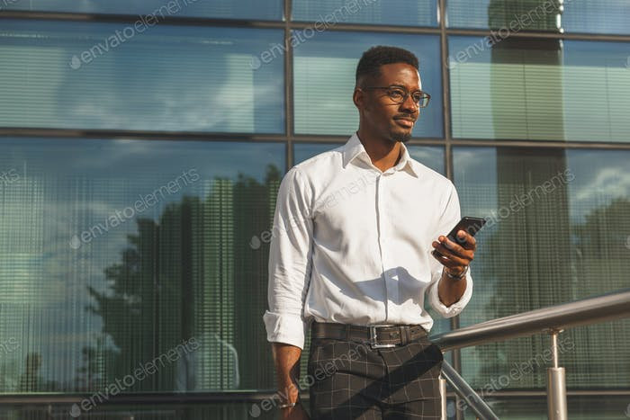 Young businessman with mobile phone in front of glass wall