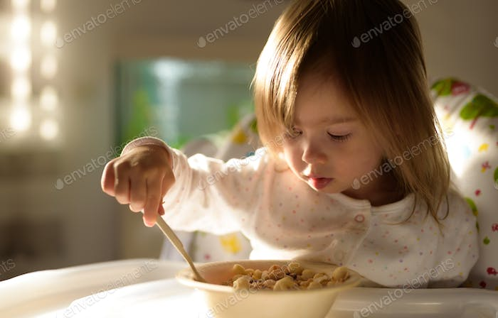 Small girl eats brakefast by herself with a spoon